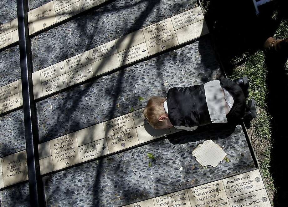 Two-year-old Nicholas Gunter of Rohnert Park lies down on memorial tiles at Sonoma State University. A sapling from the chestnut tree which gave Anne Frank hope during World War II was planted on the campus of Sonoma State in Rohnert Park, Calif., at an existing holocaust and genocide memorial Sunday April 14, 2013. Photo: Brant Ward, The Chronicle