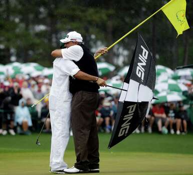 Angel Cabrera, of Argentina, hugs his caddie son Angel Cabrera, Jr. after birdie putt on the 18th hole during the fourth round of the Masters golf tournament Sunday, April 14, 2013, in Augusta, Ga. (AP Photo/David J. Phillip) Photo: David J. Phillip, Associated Press / AP