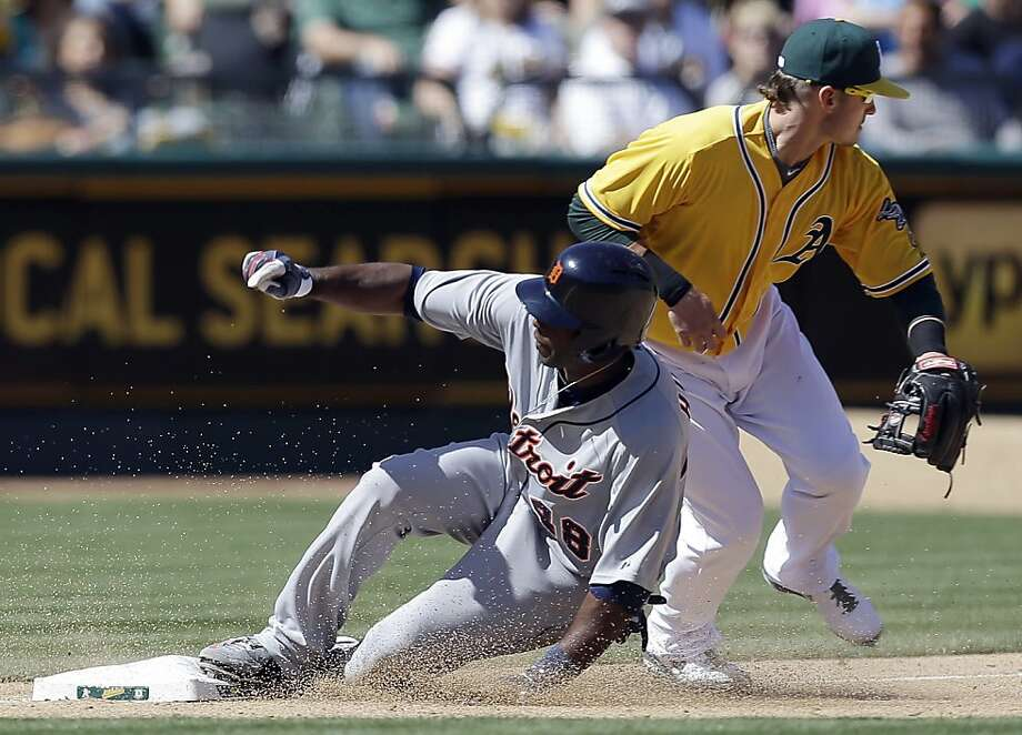 Detroit Tigers' Torii Hunter, left, slides with a triple past Oakland Athletics third baseman Josh Donaldson in the sixth inning of a baseball game on Sunday, April 14, 2013, in Oakland, Calif. (AP Photo/Ben Margot) Photo: Ben Margot, Associated Press