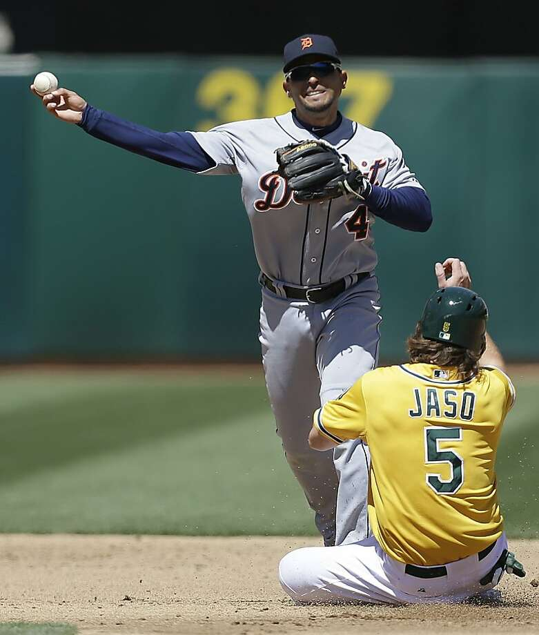 Detroit Tigers second baseman Omar Infante, top, throws over Oakland Athletics' John Jaso in the third inning of a baseball game on Sunday, April 14, 2013, in Oakland, Calif. Jaso was out on the play but A's Chris Young was safe at first base. (AP Photo/Ben Margot) Photo: Ben Margot, Associated Press