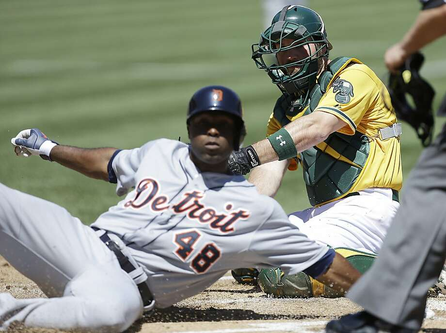 Detroit Tigers' Torii Hunter (48) slides to score past Oakland Athletics catcher Derek Norris in the first inning of a baseball game Sunday, April 14, 2013, in Oakland, Calif. Hunter scored on a single by Victor Martinez. (AP Photo/Ben Margot) Photo: Ben Margot, Associated Press