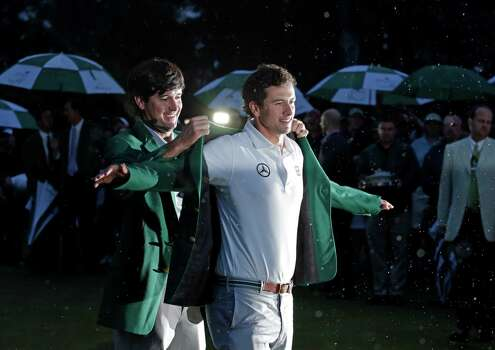 Bubba Watson, left, helps Adam Scott, of Australia, put on his green jacket after winning the Masters golf tournament Sunday, April 14, 2013, in Augusta, Ga. (AP Photo/Charlie Riedel) Photo: Charlie Riedel, Associated Press / AP
