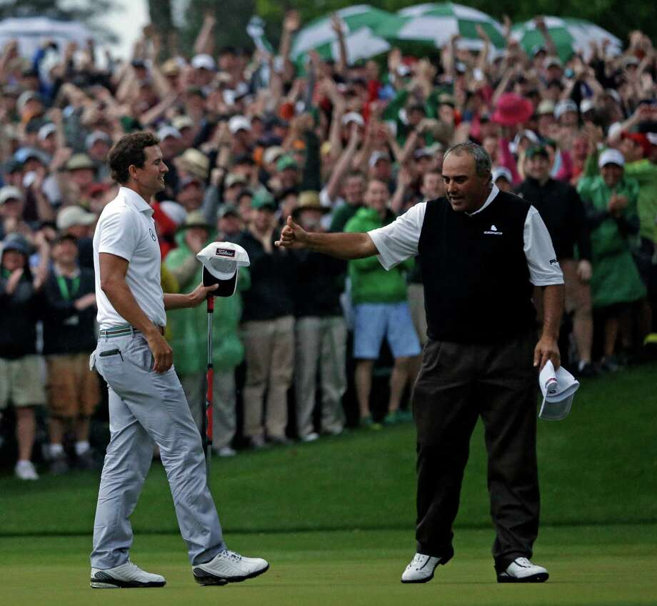 Angel Cabrera, of Argentina, gives Adam Scott, of Australia, a thumbs up after Scott made a birdie putt on the second playoff hole to win the Masters golf tournament Sunday, April 14, 2013, in Augusta, Ga. (AP Photo/David J. Phillip) Photo: David J. Phillip, Associated Press / AP