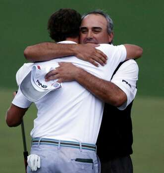 Angel Cabrera, right, of Argentina, hugs Adam Scott, of Australia, after Scott made a birdie putt on the second playoff hole to win the Masters golf tournament Sunday, April 14, 2013, in Augusta, Ga. (AP Photo/David Goldman) Photo: David Goldman, Associated Press / AP
