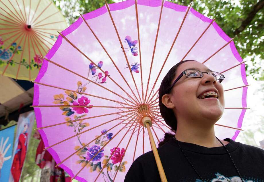 Veronica Garcia, 13, walks along with her Japanese parasol during the 20th annual Japan Festival in Hermann Park on Sunday, April 14, 2013, in Houston.  The family event featured performances of contemporary and traditional Japanese music, martial arts demonstrations, along with authentic Japanese cuisine. Photo: J. Patric Schneider, For The Chronicle / © 2013 Houston Chronicle
