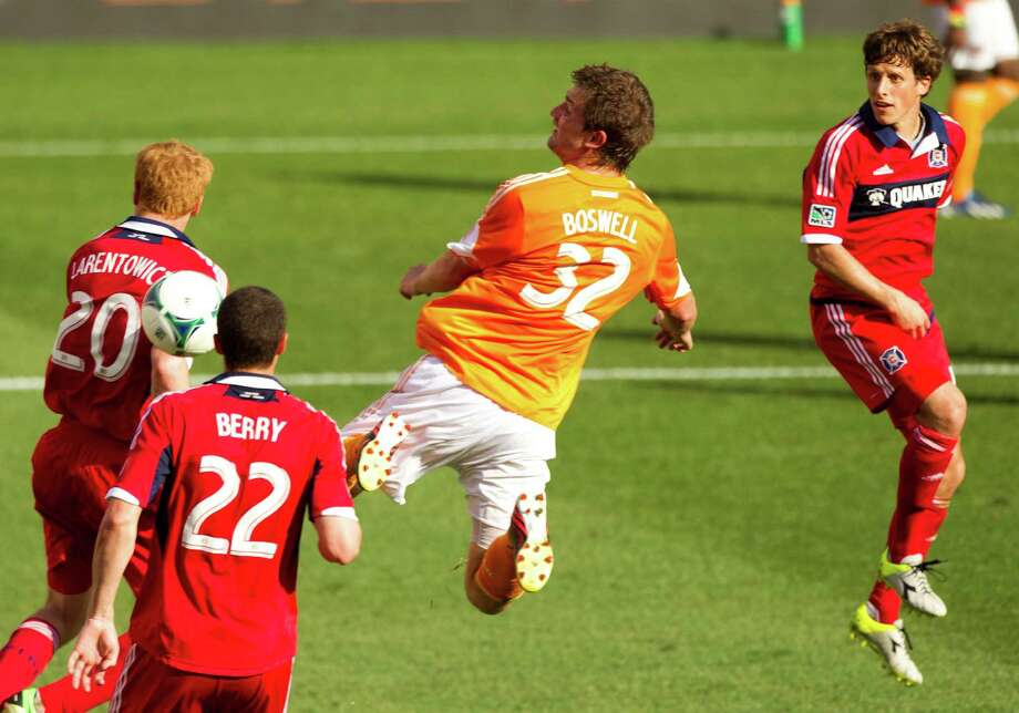 Houston Dynamo defender Bobby Boswell (32) leaps between Chicago Fire midfielder Jeff Larentowicz (20), Chicago Fire defender Austin Berry (22) and Chicago Fire midfielder Wells Thompson, right, as a free kick by Dynamo midfielder Brad Davis sails into the goal during the second half of an MLS soccer game at BBVA Compass Stadium Sunday, April 14, 2013, in Houston. The Dynamo beat the Fire 2-1 to stretch its home unbeaten streak to 35 straight games at home. Photo: Brett Coomer, Houston Chronicle / © 2013 Houston Chronicle