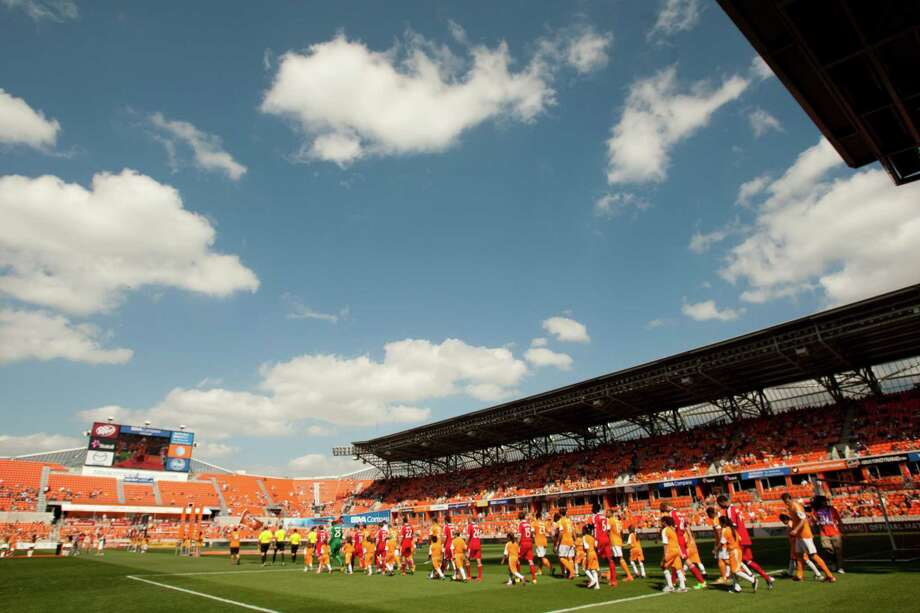 Houston Dynamo and Chicago Fire players walk onto the field at the beginning of an MLS soccer game at BBVA Compass Stadium Sunday, April 14, 2013, in Houston. The Dynamo beat the Fire 2-1 to stretch its home unbeaten streak to 35 straight games at home. Photo: Brett Coomer, Houston Chronicle / © 2013 Houston Chronicle