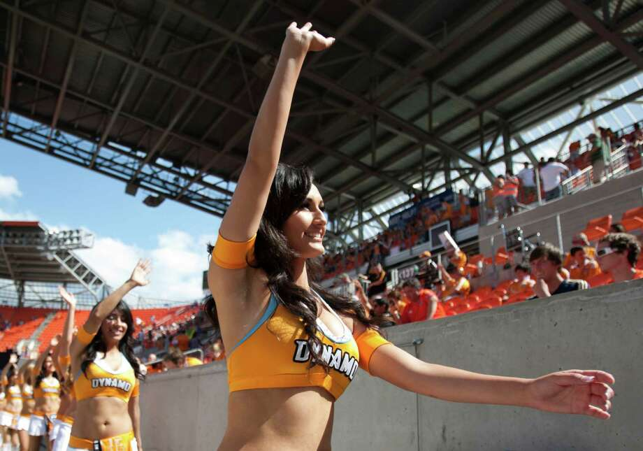 Houston Dynamo cheerleaders wave to the fans at the beginning of an MLS soccer game between the Dynamo and the Chicago Fire at BBVA Compass Stadium Sunday, April 14, 2013, in Houston. The Dynamo beat the Fire 2-1 to stretch its home unbeaten streak to 35 straight games at home. Photo: Brett Coomer, Houston Chronicle / © 2013 Houston Chronicle