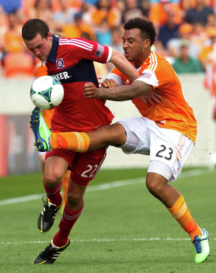 Chicago Fire defender Austin Berry (22) and Houston Dynamo midfielder Giles Barnes (23) battle for a loose ball during the first half of and MLS soccer game at BBVA Compass Stadium Sunday, April 14, 2013, in Houston. The Dynamo beat the Fire 2-1 to stretch its home unbeaten streak to 35 straight games at home. Photo: Brett Coomer, Houston Chronicle / © 2013 Houston Chronicle