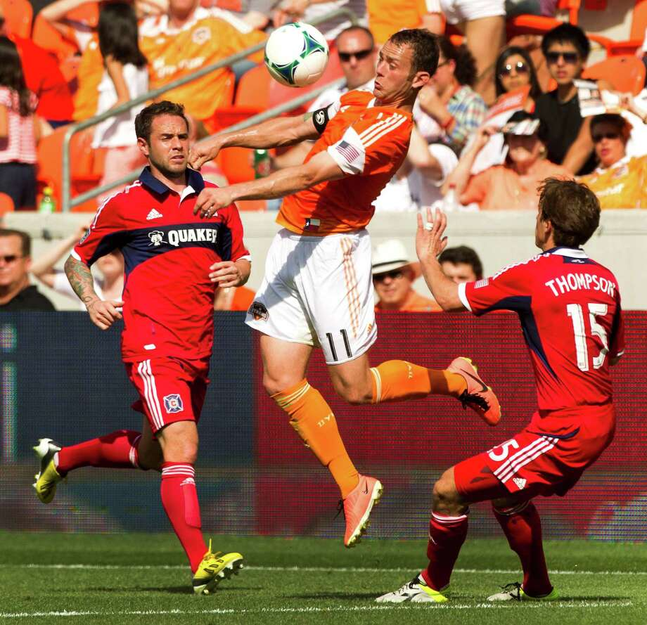 Houston Dynamo midfielder Brad Davis (11) goes up for a ball past Chicago Fire midfielder Wells Thompson (15) during the first half of and MLS soccer game at BBVA Compass Stadium Sunday, April 14, 2013, in Houston. The Dynamo beat the Fire 2-1 to stretch its home unbeaten streak to 35 straight games at home. Photo: Brett Coomer, Houston Chronicle / © 2013 Houston Chronicle