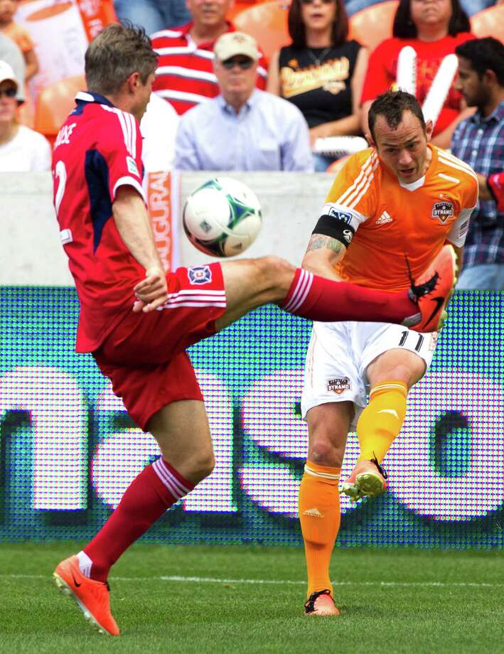 Houston Dynamo midfielder Brad Davis (11) centers a ball past Chicago Fire midfielder Logan Pause (12) during the first half of and MLS soccer game at BBVA Compass Stadium Sunday, April 14, 2013, in Houston. The Dynamo beat the Fire 2-1 to stretch its home unbeaten streak to 35 straight games at home. Photo: Brett Coomer, Houston Chronicle / © 2013 Houston Chronicle
