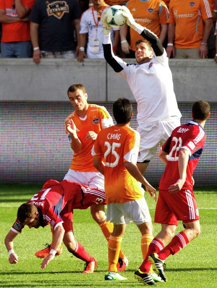 Houston Dynamo goalkeeper Tally Hall (1) leaps to grab a shot near the goal against the Chicago Fire during the second half of an MLS soccer game at BBVA Compass Stadium Sunday, April 14, 2013, in Houston. The Dynamo beat the Fire 2-1 to stretch its home unbeaten streak to 35 straight games at home. Photo: Brett Coomer, Houston Chronicle / © 2013 Houston Chronicle