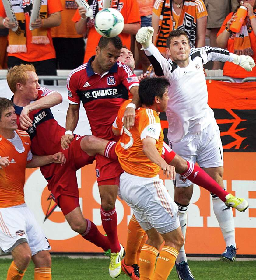 Houston Dynamo goalkeeper Tally Hall (1) knocks the ball away from the goal with Chicago Fire forward Maicon Santos (29), Fire midfielder Jeff Larentowicz (20) and Dynamo forward Brian Ching (25) going up for the ball during the second half of an MLS soccer game at BBVA Compass Stadium Sunday, April 14, 2013, in Houston. The Dynamo beat the Fire 2-1 to stretch its home unbeaten streak to 35 straight games at home. Photo: Brett Coomer, Houston Chronicle / © 2013 Houston Chronicle