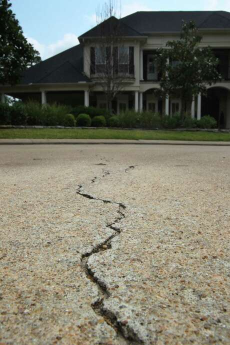 A crack in the pavement of the street outside The Woodlands home of Gordy and Michelle Bunch. Photo: Mayra Beltran, Staff / © 2013 Houston Chronicle