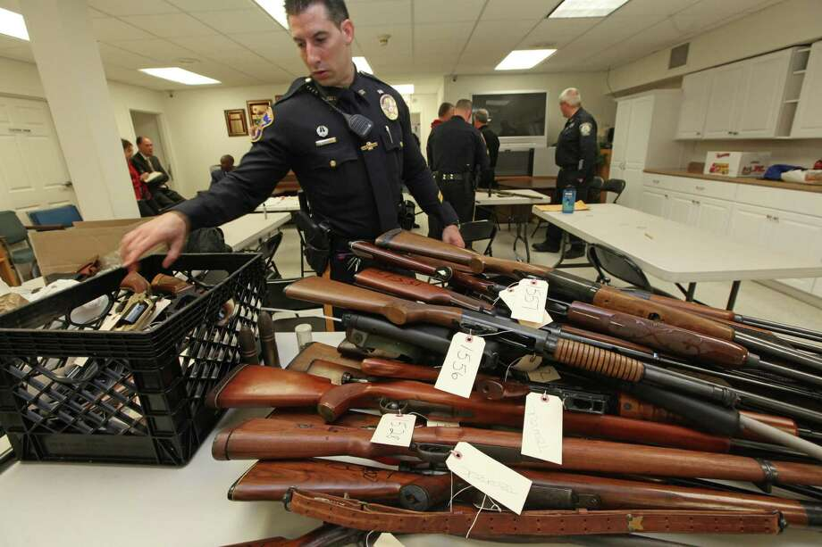 Officer Tom Richards puts another gun on a pile next to a milk crate containing handguns in the First Baptist Church of Teaneck, N.J., on Sunday. Photo: CHRIS PEDOTA, MBR / The Record
