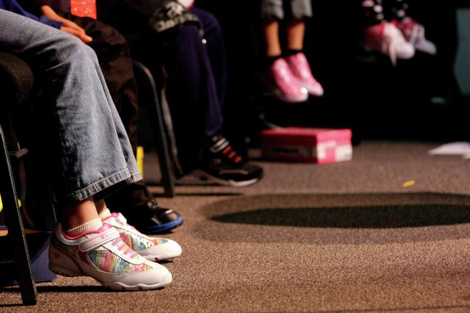 "Danielle Robinson: ""I am a shoe fanatic and one of my favorite things about going back to school was getting new sneakers. I would use that money to buy back-to-school shoes for kids around San Antonio who can't afford them, because I think everyone should be able to look forward to that experience.""PHOTO: Children from South San Filadelfia Church are given new shoes on Christmas Day 2011. Photo: Helen L. Montoya / San Antonio Express-News / SAN ANTONIO EXPRESS-NEWS"