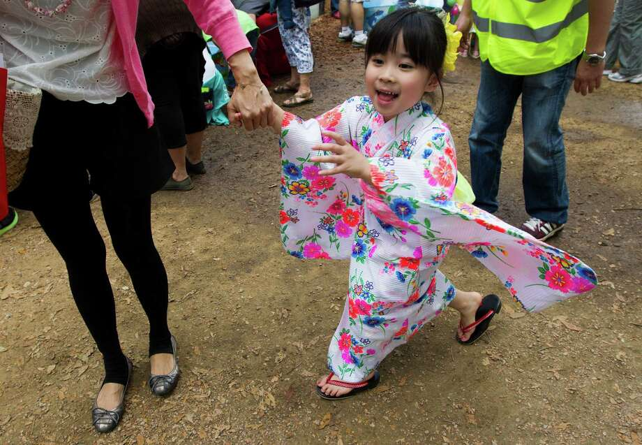 Maho Kaneko, 4, walks with her mother, Momoko, in her yukata dress during the 20th annual Japan Festival in Hermann Park on Sunday. Photo: J. Patric Schneider, Freelance / © 2013 Houston Chronicle
