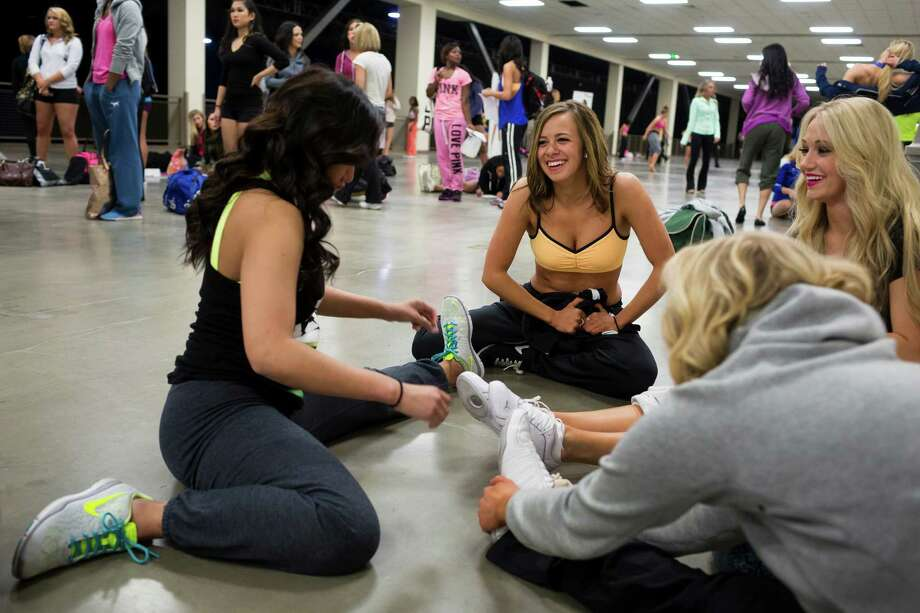 Lily Schauffle, 23, center right, laughs with a group of friends while stretching out before the first round of open Sea Gals auditions Sunday, April 14, 2013, at the CenturyLink Field Event Center in Seattle. Contestants were judged on dance ability, pizzazz and physical appearance. Nearly half of the attendees made the preliminary cut. Photo: JORDAN STEAD / SEATTLEPI.COM
