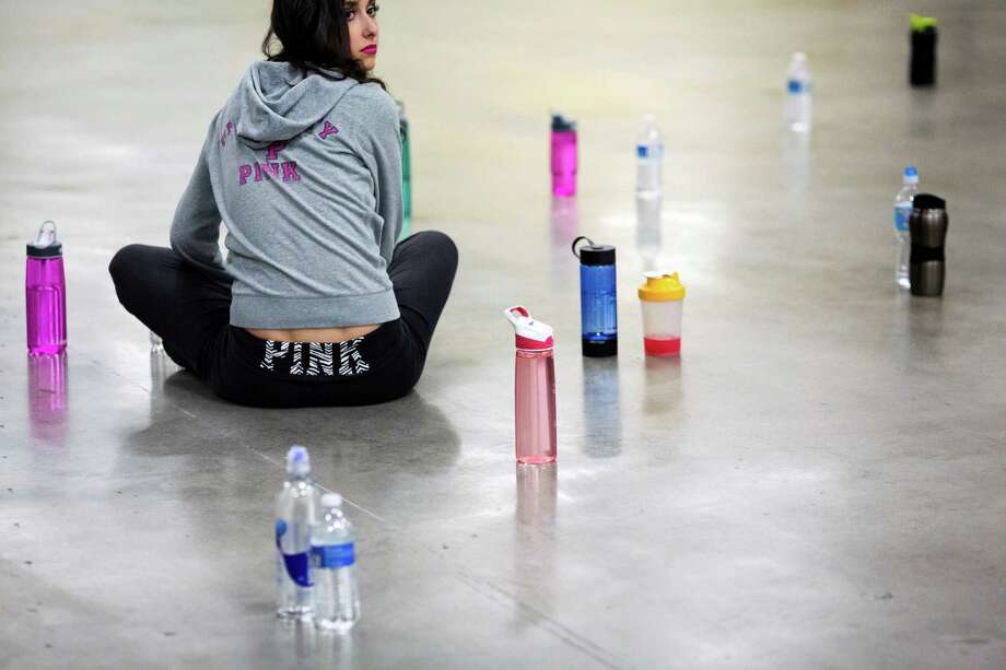 A lone contestant keeps watch over surrounding water bottles during an attendee-wide bathroom break during the first round of open Sea Gals auditions Sunday, April 14, 2013, at the CenturyLink Field Event Center in Seattle. Contestants were judged on dance ability, pizzazz and physical appearance. Nearly half of the attendees made the preliminary cut. Photo: JORDAN STEAD / SEATTLEPI.COM