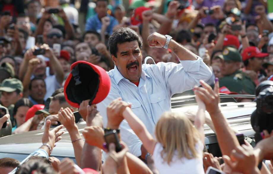 Venezuelan interim President Nicolas Maduro gestures to supporters as he leaves the polls on Sunday. Photo: Ariana Cubillos, STF / AP
