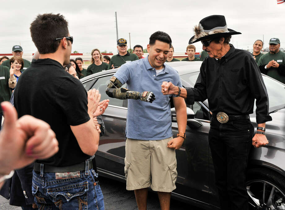 Wounded veteran Sebastian Gallegos fist-bumps with NASCAR legend Richard Petty after receiving a new car at the San Antonio Speedway. NASCAR driver Aric Almirola is at left. Photo: Photos By Robin Jerstad / For The San Antonio Express-News