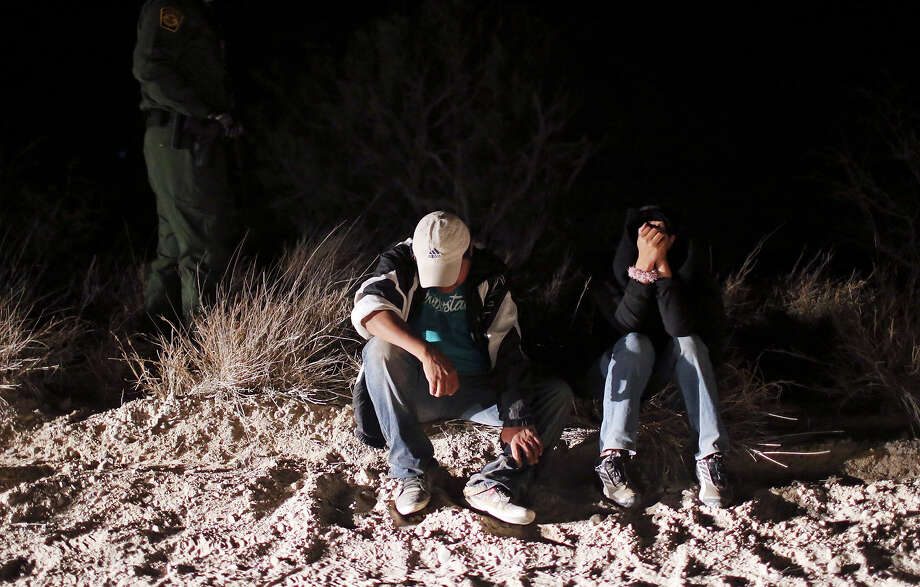 A Border Patrol agent (left rear) watches over undocumented immigrants from Mexico after they were caught along Military Road near La Joya earlier this month. Photo: Edward A. Ornelas, Staff / © 2013 San Antonio Express-News
