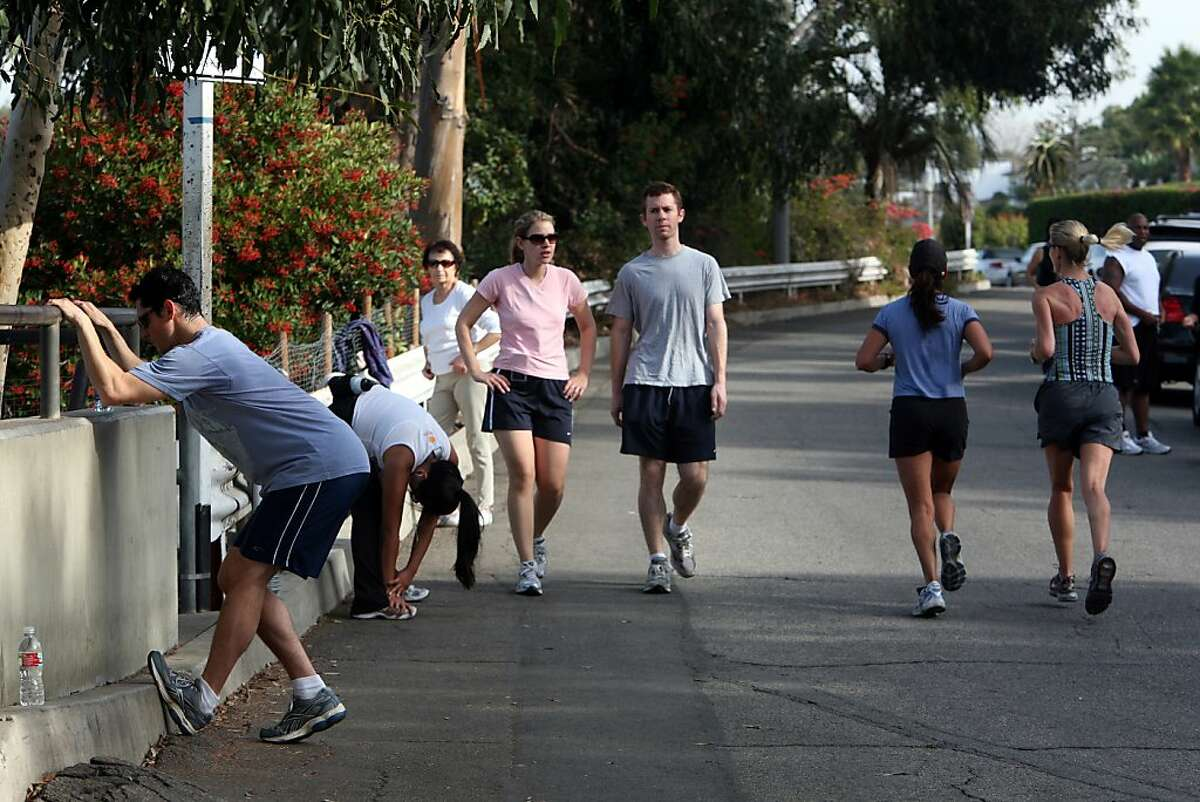 (NYT42) SANTA MONICA, Calif. -- Nov. 24, 2008 -- CALIF-EXERCISE-POLICE-4 -- People walking, jogging and running, near the corner of 4th Street and Adelaide Drive, Nov. 19, 2008. In the last six months, park rangers, dispatched by the Santa Monica Police Department in response to complaining neighbors, have parked themselves on the corner during much of the day, at the ready to break up any unauthorized tai chi. The reason is the increasingly loud, littering and generally intrusive groups of exercisers who gather from dawn until dusk along the 4th Street median strip, interfering with the view of the Pacific Ocean and transforming the area into a huge outdoor gym rimmed by multimillion-dollar homes. (Monica Almeida/The New York Times)