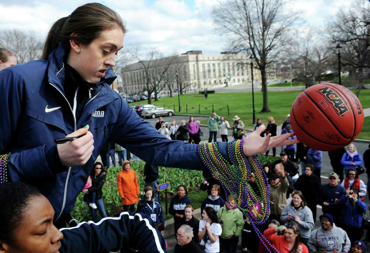 Connecticut's Breanna Stewart, the Most Outstanding Player in the women's NCAA Tournament, tosses a signed basketball to a fan during a parade in Hartford, Conn., on Sunday honoring the national champions.