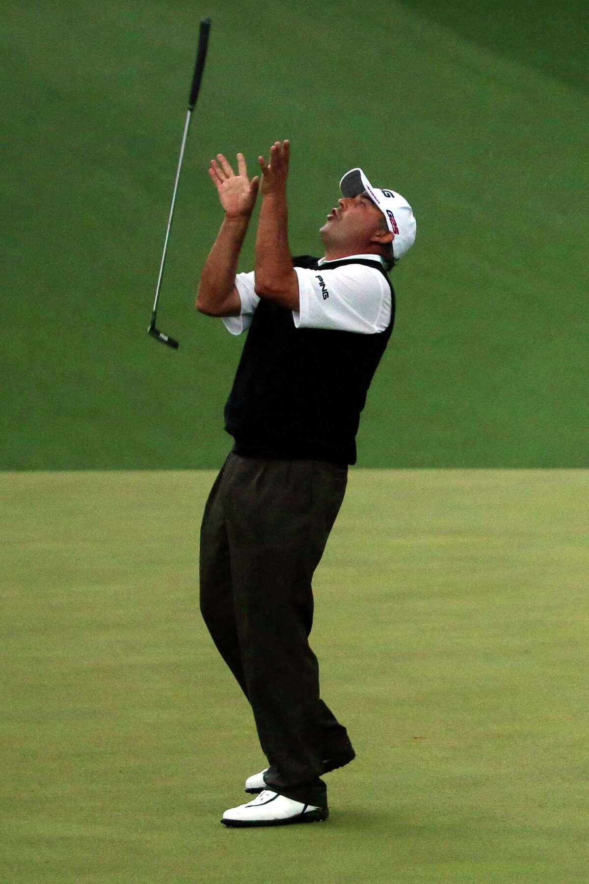 Angel Cabrera catches his putter after narrowly missing a birdie putt on the second playoff hole.
