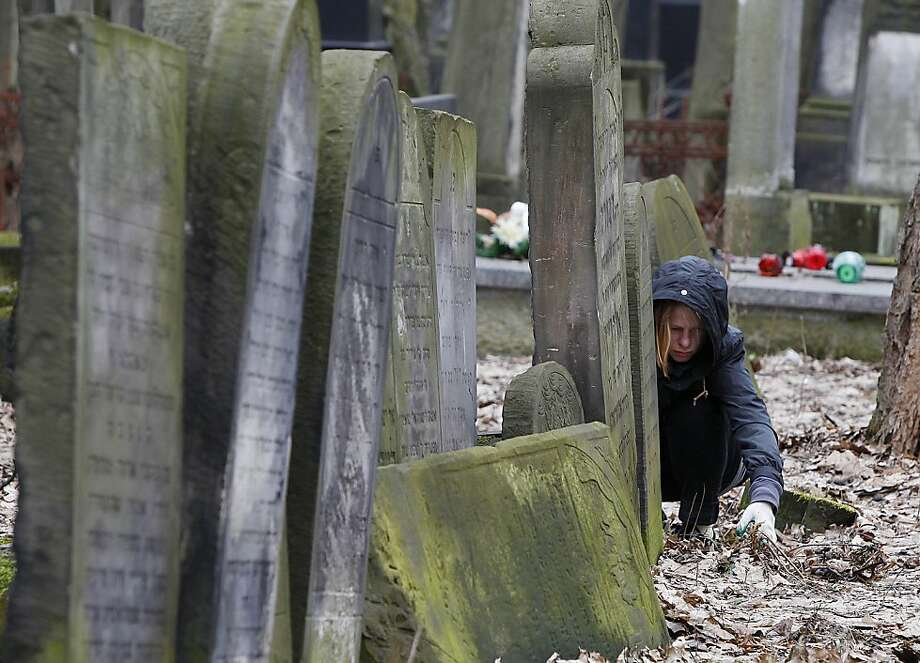 A volunteer helps to clean a Jewish cemetery in Warsaw, Poland, on Sunday April 14, 2013. The volunteers are answering a call by Polish officials to help clean the Okopowa Street Jewish Cemetery as the city launches a month of commemorative events marking the 70th anniversary of the Warsaw Ghetto Uprising. The events come amid a growing inclination in Poland to celebrate the country's Jewish history. (AP Photo/Czarek Sokolowski) Photo: Czarek Sokolowski, Associated Press