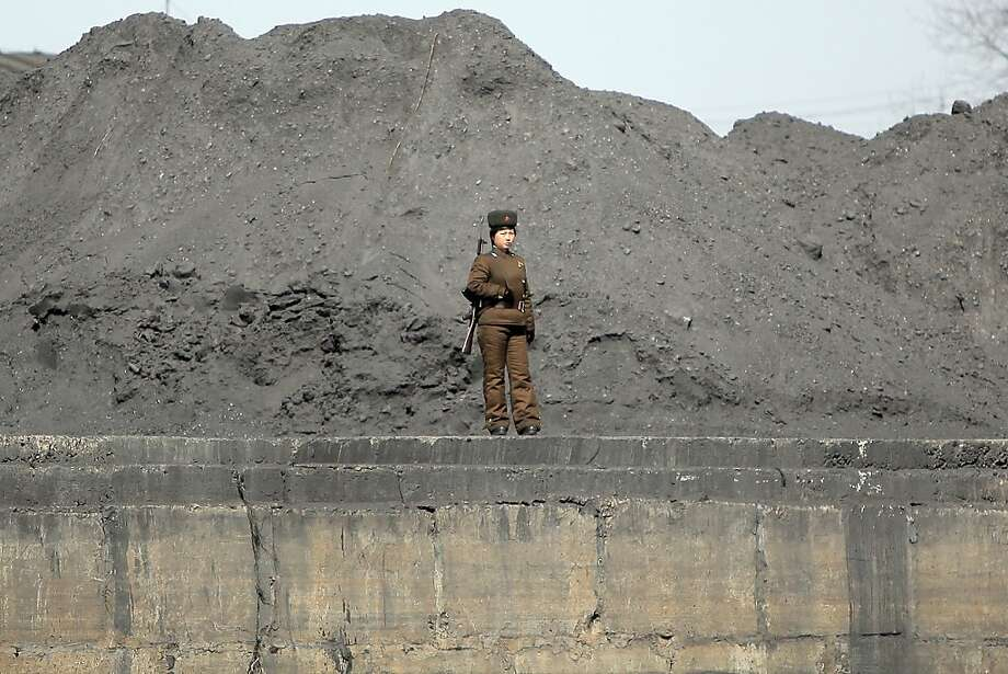 This picture taken on April 14, 2013 shows a woman North Korean soldier patrols along the bank of the Yalu River in the North Korean town of Sinuiju across from the Chinese city of Dandong. US Secretary of State John Kerry said he would be prepared to reach out to Pyongyang urging it back to negotiations, as he vowed Washington would protect Japan from North Korea's threats.            CHINA OUT      AFP PHOTOSTR/AFP/Getty Images Photo: Str, AFP/Getty Images