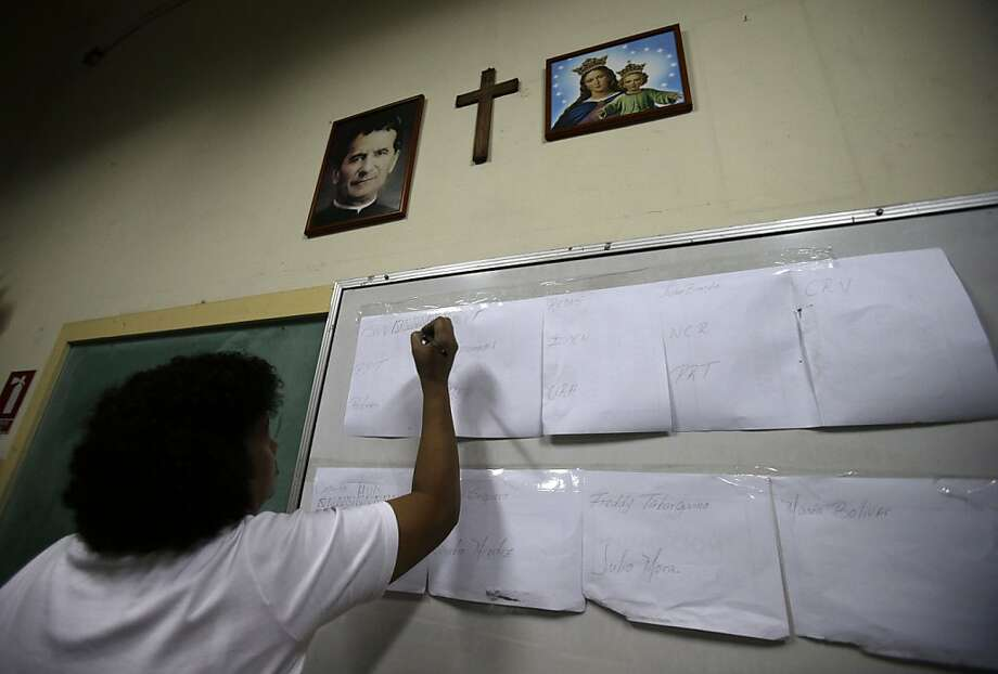 A polling station delegate writes down counted votes on a board at a polling station set up at the San Francisco de Sales school in Caracas, Venezuela, Sunday, April 14, 2013. Venezuelans went to the polls Sunday to choose the next president between Hugo Chavez's chosen successor, ruling party candidate Nicolas Maduro, and opposition candidate Henrique Capriles. (AP Photo/Fernando Llano) Photo: Fernando Llano, Associated Press