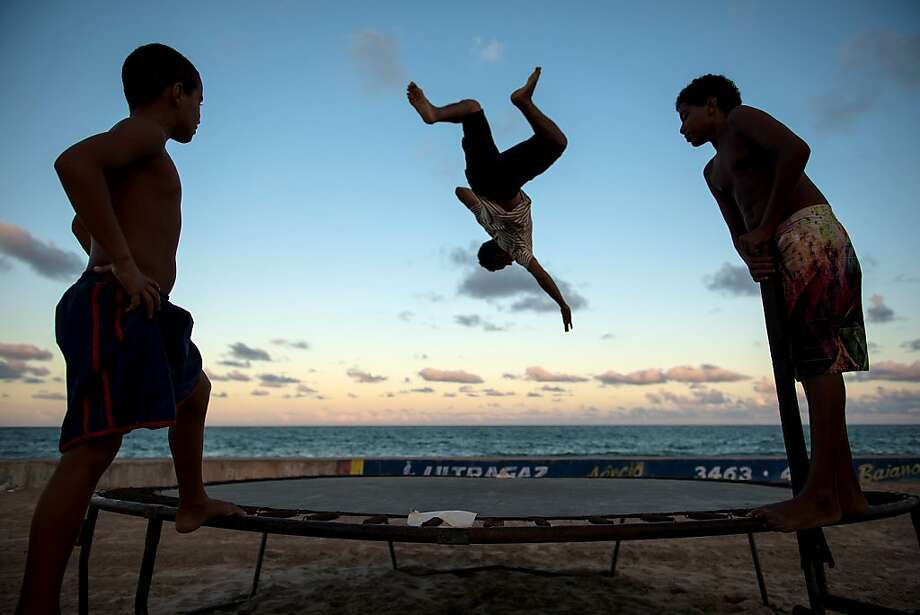Kids play on a trampoline on the beach in Recife, Pernambuco state, Brazil on April 14, 2013. AFP PHOTO/Yasuyoshi CHIBAYASUYOSHI CHIBA/AFP/Getty Images Photo: Yasuyoshi Chiba, AFP/Getty Images
