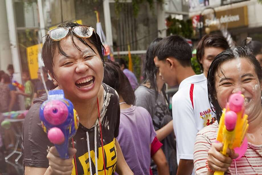 Bang! You're wet:Thai New Year's revelers shoot a photographer shooting them during the Songkran water festival, the annual community water fight celebrating the holiday. Dousing people is considered a way of paying respect to them and is meant as a symbol of cleansing and purification. Photo: Jack Kurtz, Getty Images