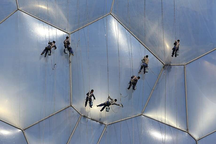 BEIJING, CHINA - APRIL 14:  Chinese workers clean the bubble shaped surface of the National Aquatics Center, known as the Water Cube, on April 14, 2013 in Beijing, China. The Aquatics Center hosted the swimming, diving and Synchronized Swimming events during Beijing Olympic Games.  (Photo by Feng Li/Getty Images) *** BESTPIX *** Photo: Feng Li, Getty Images