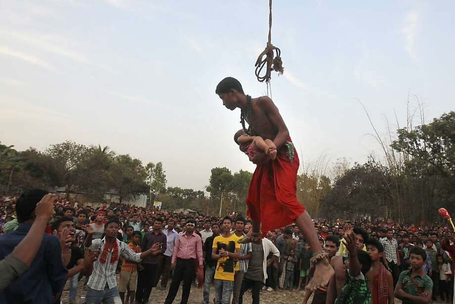 A Bangladeshi Hindu devotee carries a child as he hangs in a rope with hooks pierced in his back as part of a ritual during the Charak Puja festival in Dhaka, Bangladesh, Sunday, April 14, 2013. (AP Photo/A.M. Ahad) Photo: A.M. Ahad, Associated Press