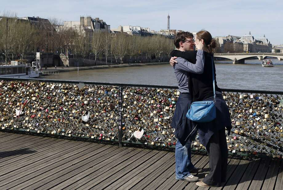 A couple kisses after hanging a love padlock on the steel bar  of the Pont des Arts on April 14, 2013 in Paris. AFP PHOTO / PATRICK KOVARIKPATRICK KOVARIK/AFP/Getty Images Photo: Patrick Kovarik, AFP/Getty Images