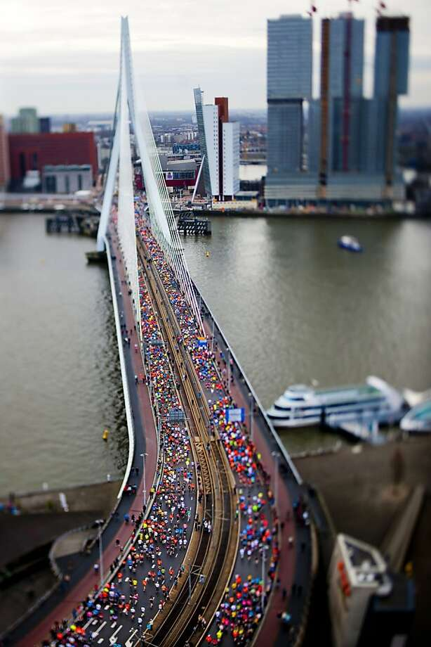 A picture taken with a tilt-shift lens shows runners crossing the Erasmus Bridge in Rotterdam during the Rotterdam Marathon on April 14, 2013. AFP PHOTO / ANP / ROBIN UTRECHT 