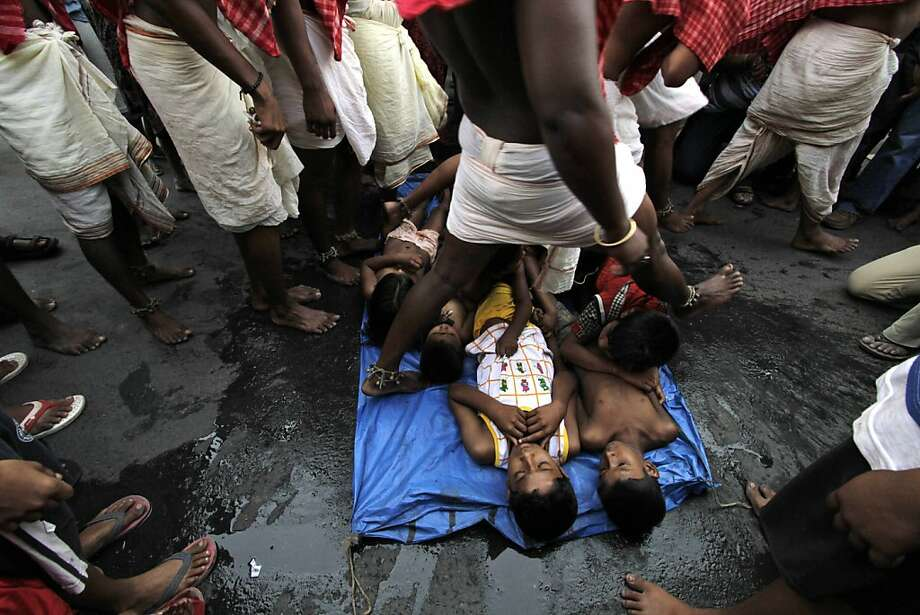Children are laid on a road as Hindu devotees step over them as part of a ritual during celebration of Shiva Gajan, a Hindu festival in Kolkata, India, Sunday, April 14, 2013. Devotees of Hindu god Shiva believe performing this ritual will ensure fulfillment of their wishes. (AP Photo/Bikas Das) Photo: Bikas Das, Associated Press