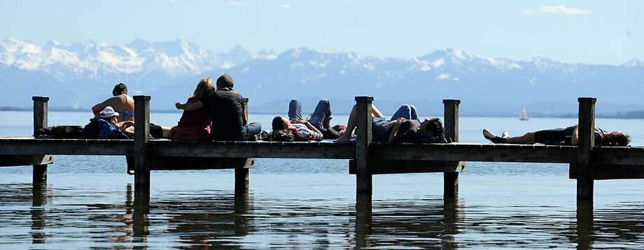 People enjoy the sun shine on a pier at Starnberger See, southern Germany on April 14, 2013 as temperatures rose to up to 20 degrees Celsius. AFP PHOTO / ANDREAS GEBERT  GERMANY OUTANDREAS GEBERT/AFP/Getty Images Photo: Andreas Gebert, AFP/Getty Images