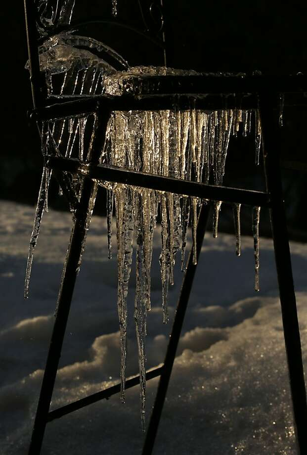 The setting sun highlights ice hanging from an outdoor chair, Saturday, April 13, 2013, in Weston, Wis. Melting snow from a porch above drips on the chair and then forms icicles when the temperature dips below freezing. (AP Photo/Daily Herald Media, Dan Young) Photo: Dan Young, Associated Press