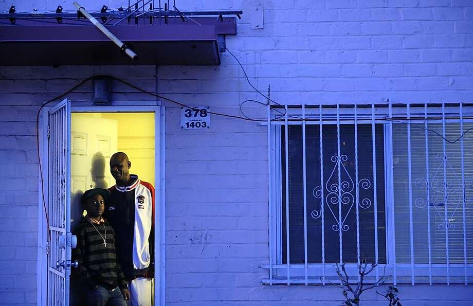 Jeff Littrel and his son, Malik, stand in the doorway of their home in the Ramona Gardens housing project in Los Angeles, California. The pair have settled in the troubled racially-troubled neighborhood and have become part of the community. (Wally Skalij/Los Angeles Times/MCT) Photo: Wally Skalij, McClatchy-Tribune News Service