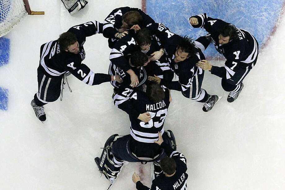 Yale goalie Jeff Malcolm (33) is swarmed by teammates after shutting out Quinnipiac 4-0 to win the NCAA men's college hockey national championship game in Pittsburgh Saturday, April 13, 2013.  (AP Photo/Gene Puskar) Photo: Gene Puskar, Associated Press