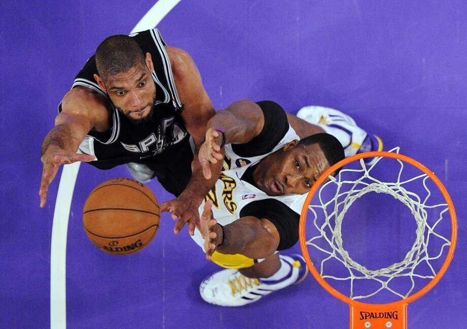 Spurs forward Tim Duncan (left) shoots as Los Angeles Lakers center Dwight Howard defends during the first half  Sunday, April 14, 2013, in Los Angeles.