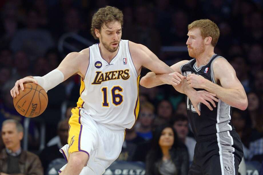 Los Angeles Lakers forward Pau Gasol (16) drives toward the basket as Spurs forward Matt Bonner defends during the first half  Sunday, April 14, 2013, in Los Angeles.