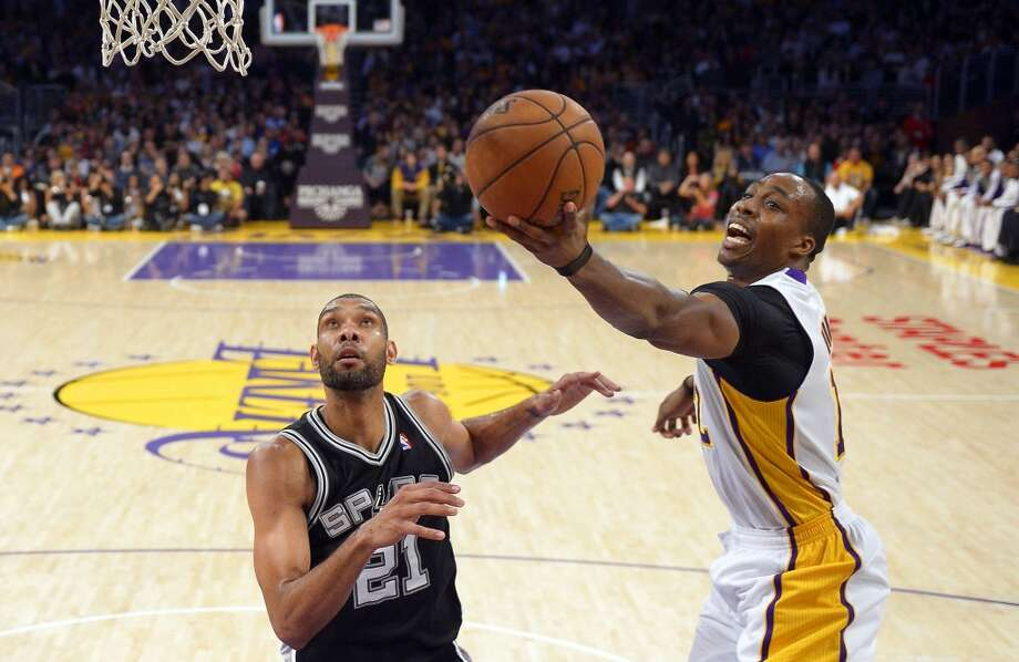Los Angeles Lakers center Dwight Howard (right) shoots as Spurs forward Tim Duncan defends during the first half Sunday, April 14, 2013, in Los Angeles.