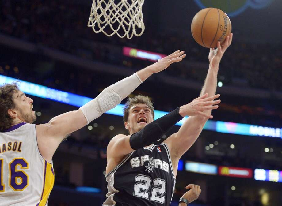 Spurs center Tiago Splitter (right) shoots as Los Angeles Lakers forward Pau Gasol defends during the first half  Sunday, April 14, 2013, in Los Angeles.