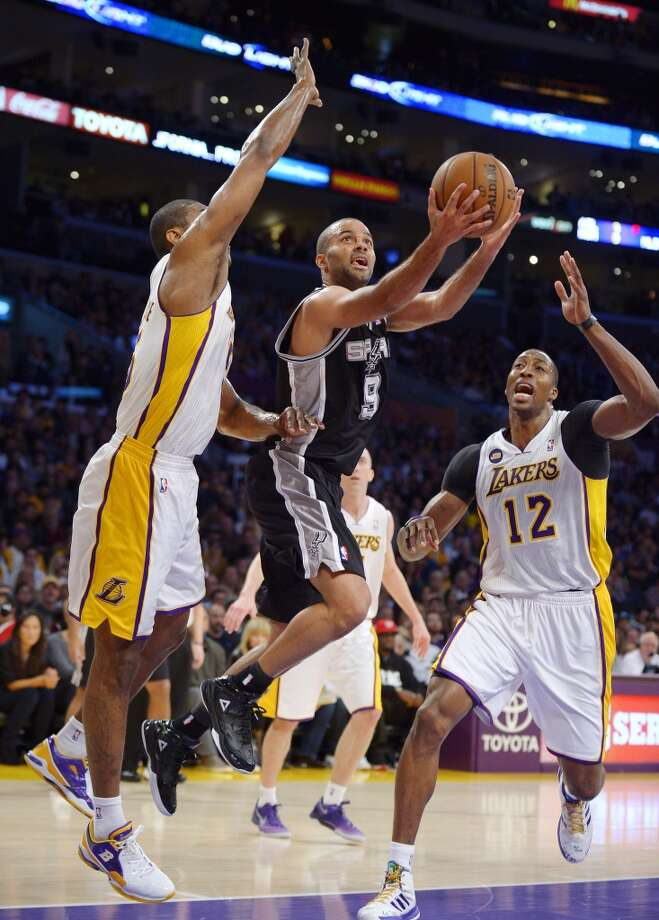 Spurs guard Tony Parker (center)  shoots as Los Angeles Lakers forward Metta World Peace (left) and center Dwight Howard defend during the first half Sunday, April 14, 2013, in Los Angeles.