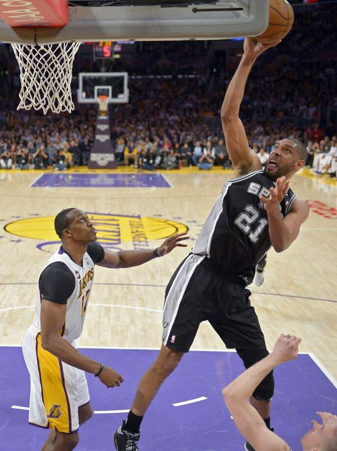 Spurs forward Tim Duncan puts up a shot as Los Angeles Lakers center Dwight Howard looks on during the second half  Sunday, April 14, 2013, in Los Angeles. The Lakers won 91-86.
