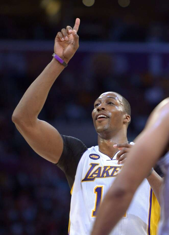 Los Angeles Lakers center Dwight Howard points to the sky after making a free throw during the second half  against the Spurs, Sunday, April 14, 2013, in Los Angeles. The Lakers won 91-86.
